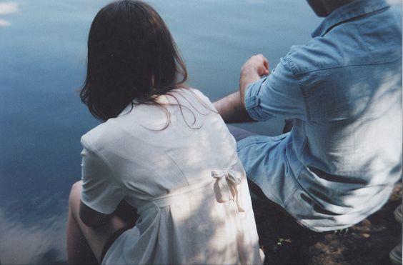 Paar sitzt nebeneinander am Wasser