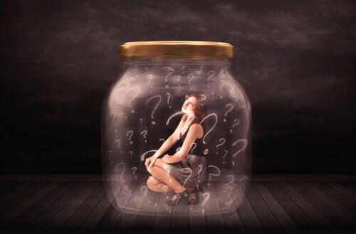 Frau in einem Einmachglas voller Fragezeichen