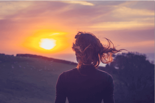 Frau schaut Sonnenaufgang zu