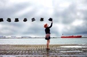 Hilfreiche Gesprächsthemen - Frau steht am Wasser und über ihr schweben mehrere Hüte