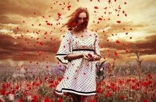 Frau, die von roten Blumen umgeben ist und Blütenblätter verstreut
