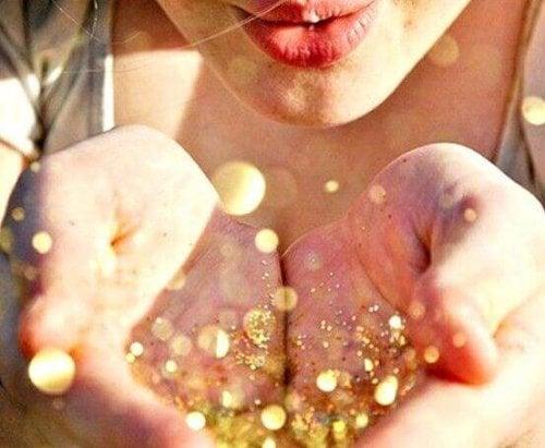 Frau pustet goldenen Glitzer