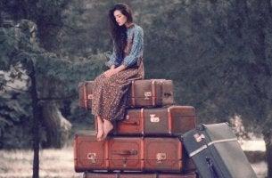 Was ist Reife? - Frau, die auf Koffern sitzt, in die sie ihr Leben gepackt hat
