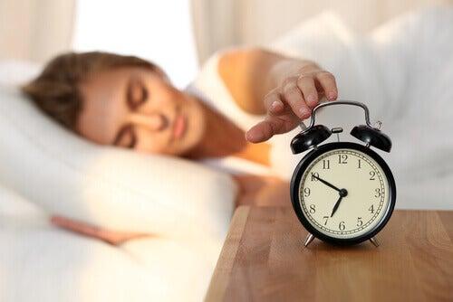 Frau liegt im Bett und schaltet den Wecker aus