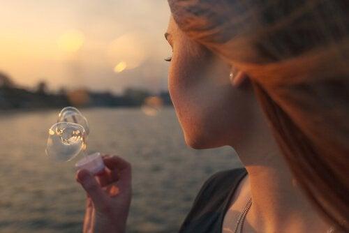 Jemanden zurückwollen - Frau macht Seifenblasen, die vom Wind fortgetragen werden