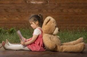 Vermeidende Bindung - Kind sitzt Rücken an Rücken mit einem Teddybär