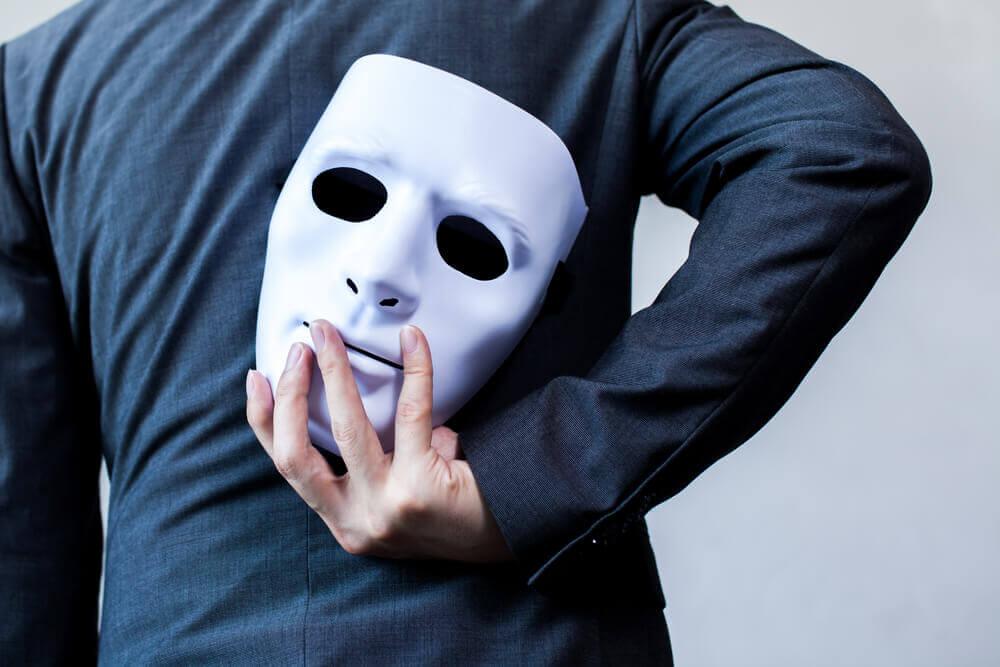 Mann hält Maske hinter dem Rücken