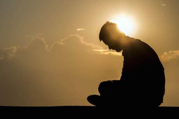 Trauriger Mann sitzt vor untergehender Sonne