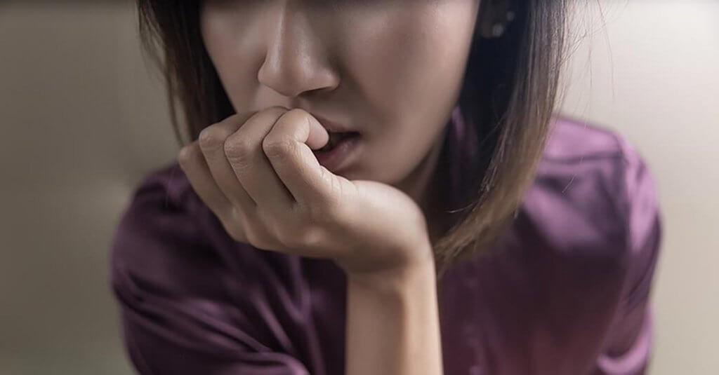 Ängstliche Frau knabbert an ihren Fingernägeln