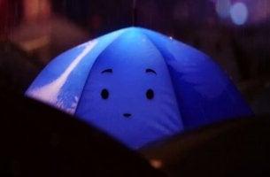 Wie man sich Menschen mit Autismus gegenüber verhalten sollte - blauer Regenschirm mit traurigem Gesicht