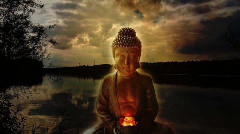 Die Statue eines Buddhas vor Abendstimmung am Fluss.