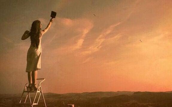 Mädchen streicht den Himmel an