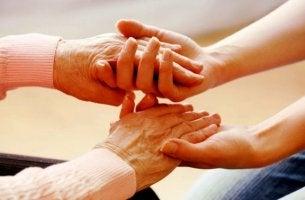 Sich um andere kümmern - junge Hände halten alte Hände