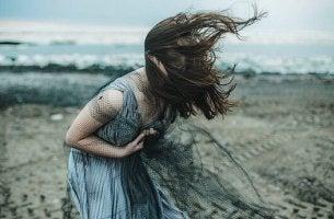 Selbstzerstörerische Menschen - Frau vornübergebeugt am Strand