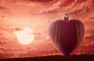 Gesunde Liebesbeziehung - Paar ist gemeinsam auf ein Herz geklettert.