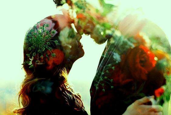 Paar tauscht Zärtlichkeiten aus, bedeckt mit Blüten und Gräsern.