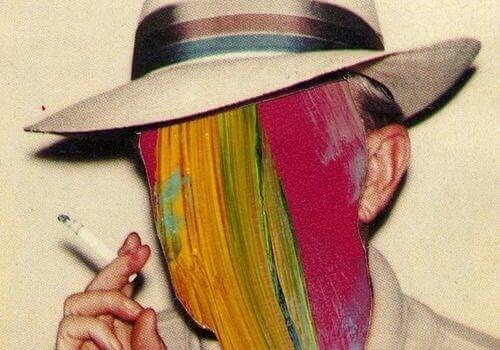 Rauchender Mann mit Hut, dessen Gesicht mit bunten Farben übermalt ist