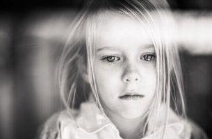 Ein Kind, das nicht geliebt wird - Trauriges Mädchen blickt durch's Fenster.