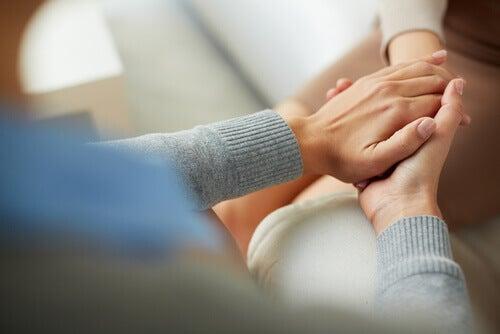 Tröstend die Hand halten