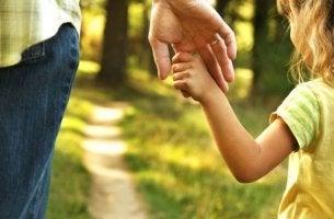 Vertrauen verdienen - Tochter hält Hand des Vaters voller Vertrauen
