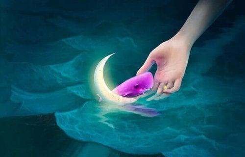 Hände greifen nach pinkfarbenem Wal auf dem Mond