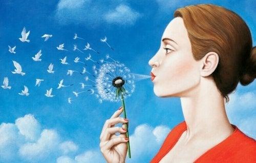 Frau, die gegen eine Pusteblume bläst, aus der Tauben aufsteigen