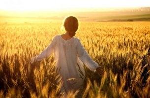 Natürliche Heilmittel gegen die Depression - Frau, die durch ein Weizenfeld läuft