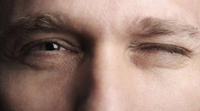 Mann kneift ein Auge zu