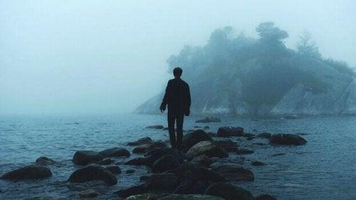Mann, der auf Steinen das Meer überquert