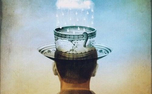 Mann mit einer Teetasse auf dem Kopf, die Regentropfen sammelt