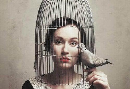 Frau im Vogelkäfig mit Taube in der Hand