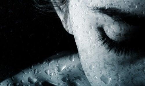 Frau mit geschlossenen Augen hinter nasser Scheibe
