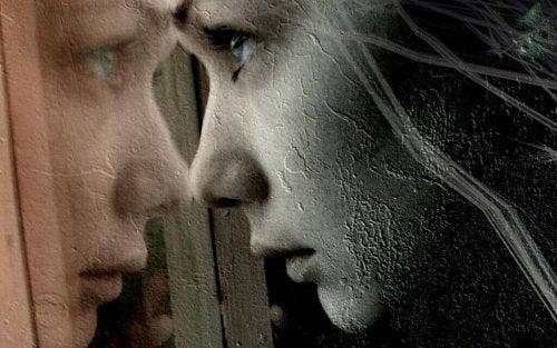 Frau schaut voller Schmerz in den Spiegel