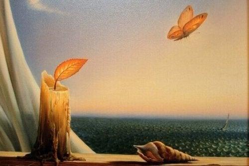 Kerze mit einem Blatt als Docht und Schmetterling