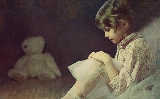 Unsichere Bindung - Mädchen sitzt neben einem Teddybären