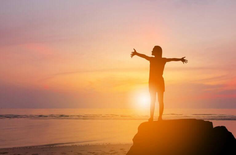 Frau bei Sonnenaufgang am Meer