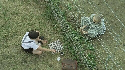 Bruno und Shmuel spielen Schach, zwischen ihnen ein Stacheldrahtzaun