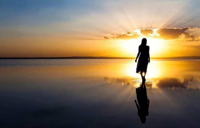 Frau bei Sonnenaufgang am Strand