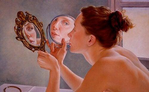 Frau betrachtet sich selbst in zwei Spiegeln