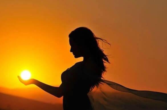 Frau hält Sonne in der Hand