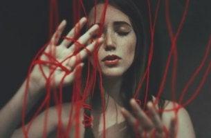 Keine Liebe? - Frau in einem Netz aus roten Fäden