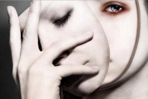 Wo sitzt die Persönlichkeit? - Frau mit zwei Gesichtern nimmt eine Maske ab