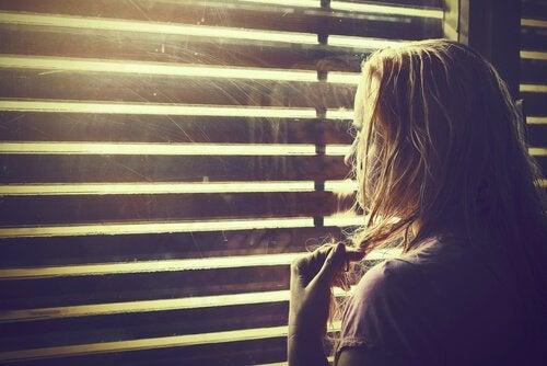 Eine Frau schaut durch die Jalousien eines Fensters nach draußen.