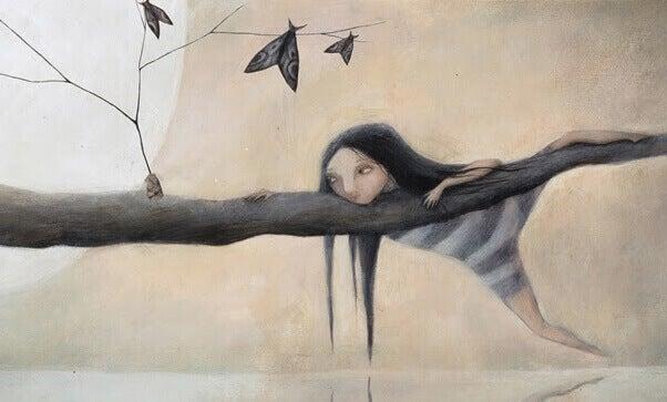 Mädchen hängt auf einem Baumstamm