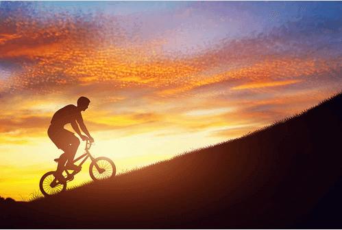 Mann fährt im Sonnenuntergang auf dem Fahrrad einen Berg hinauf.