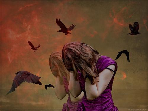 Verstörte Frau umgeben von Raben