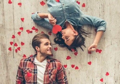 Paar, das mit Herzen auf dem Boden liegt