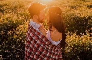 Sprachen der Liebe - Paar, das eingewickelt in einer Decke auf einem Feld steht