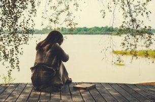 Phasen des Schmerzes nach einer Trennung - Frau sitzt am Wasser