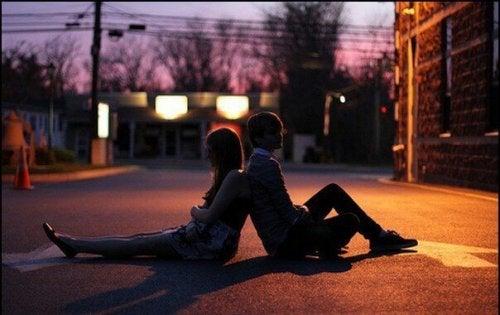 Paar, das Rücken an Rücken auf der Straße sitzt